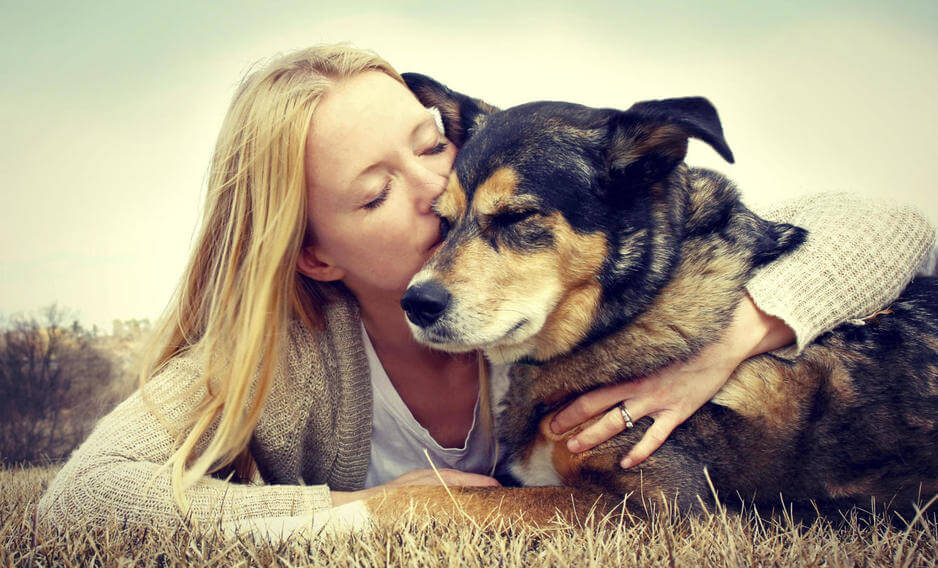 Mujer dándole un beso a su perro