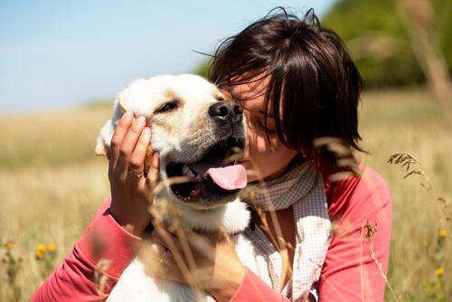 woman hugging dog in field