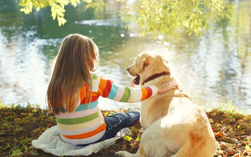 Perro con una niña en el lago