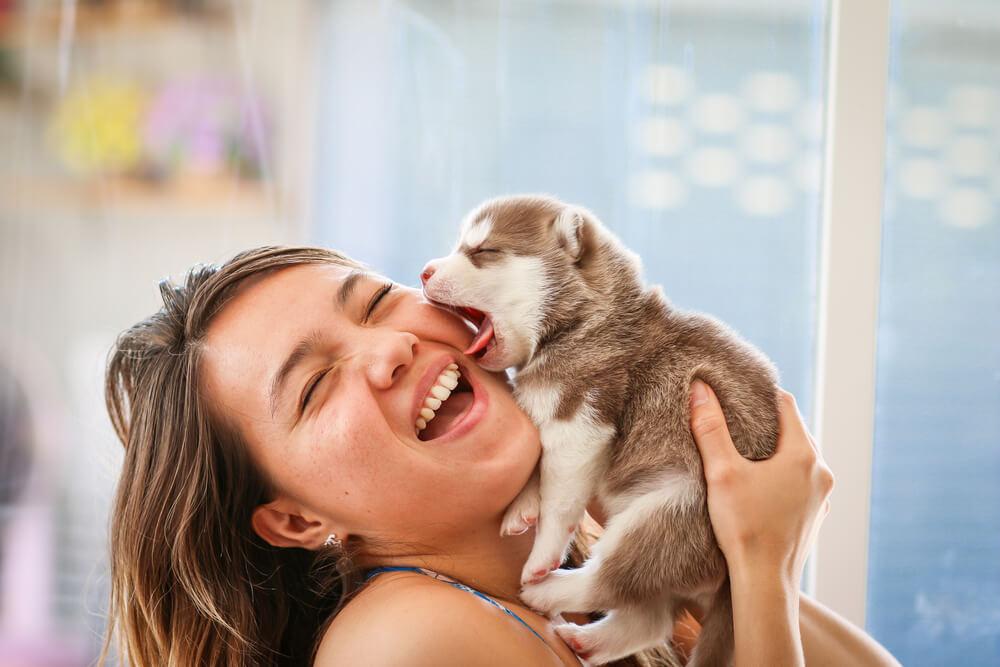 Mujer sonriendo con cachorro.