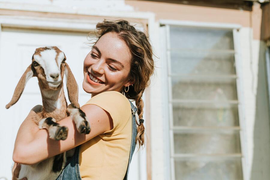 Chica con cabra en brazos