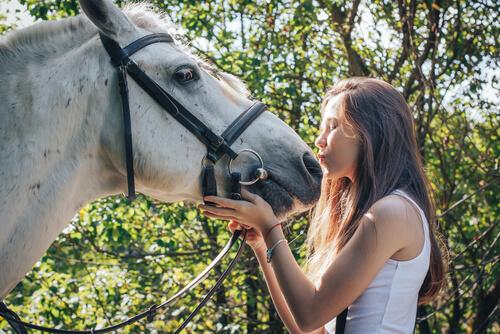 Chica dándole un beso a su caballo (terapia equina).