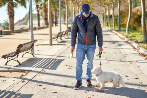 Hombre sacando a la mascota a pasear durante la cuarentena.