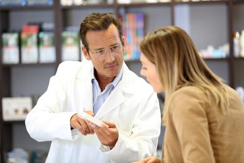 Veterinario asesorando sobre medicamentos a una tutora.