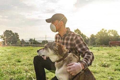 Un chico con mascarilla paseando a su perro.