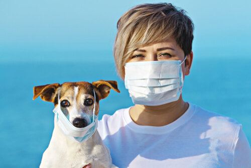 Una mujer y un perro con mascarilla.