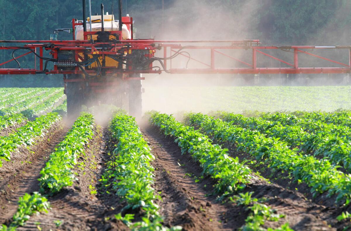 Un tractor con plaguicida rociando un cultivo.