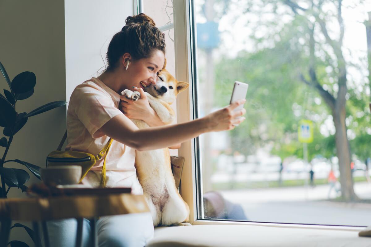 Una mujer se hace una foto con un perro en una cafetería.