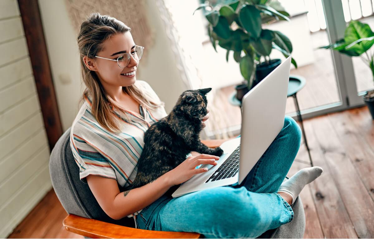 Una mujer mira a un ordenador con su gato.