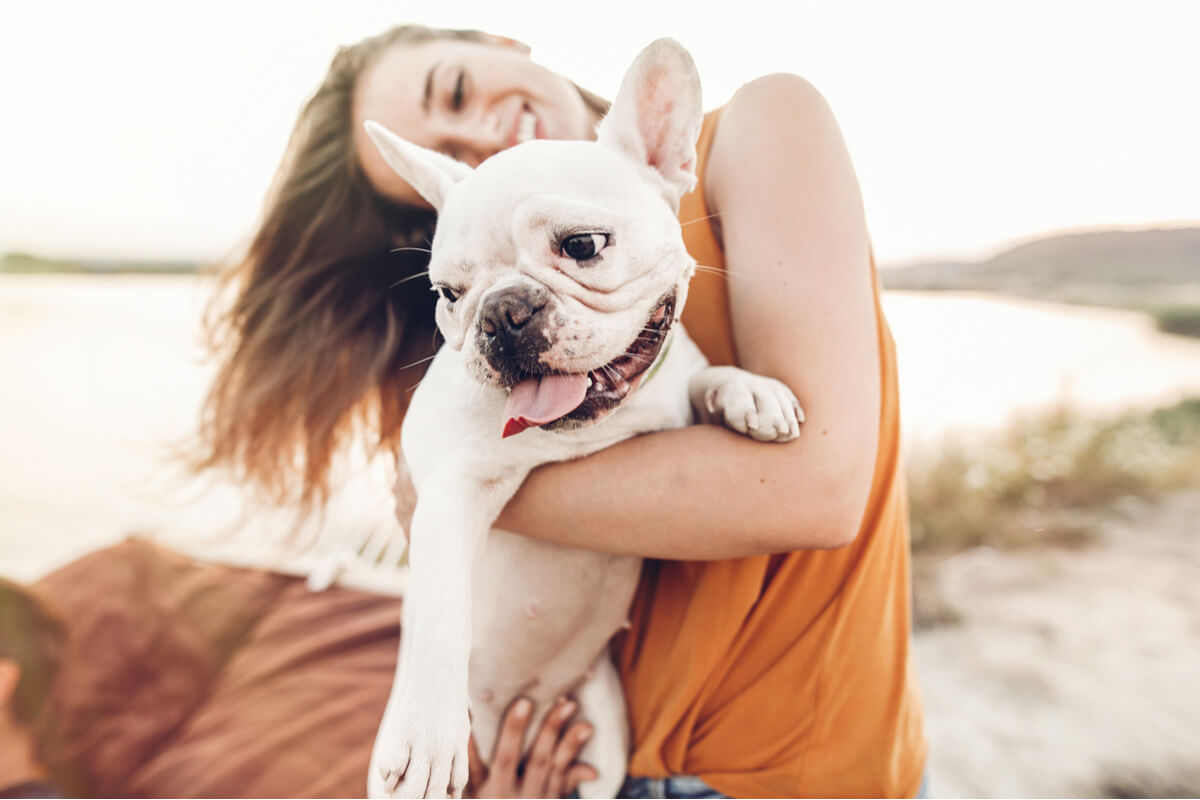 Un perro en la playa con su dueña.