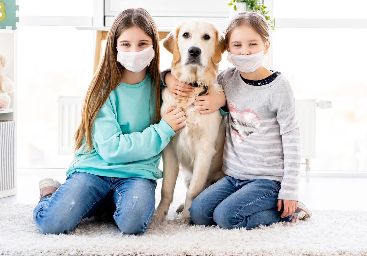 Unas niñas con mascarilla abrazando a un perro.