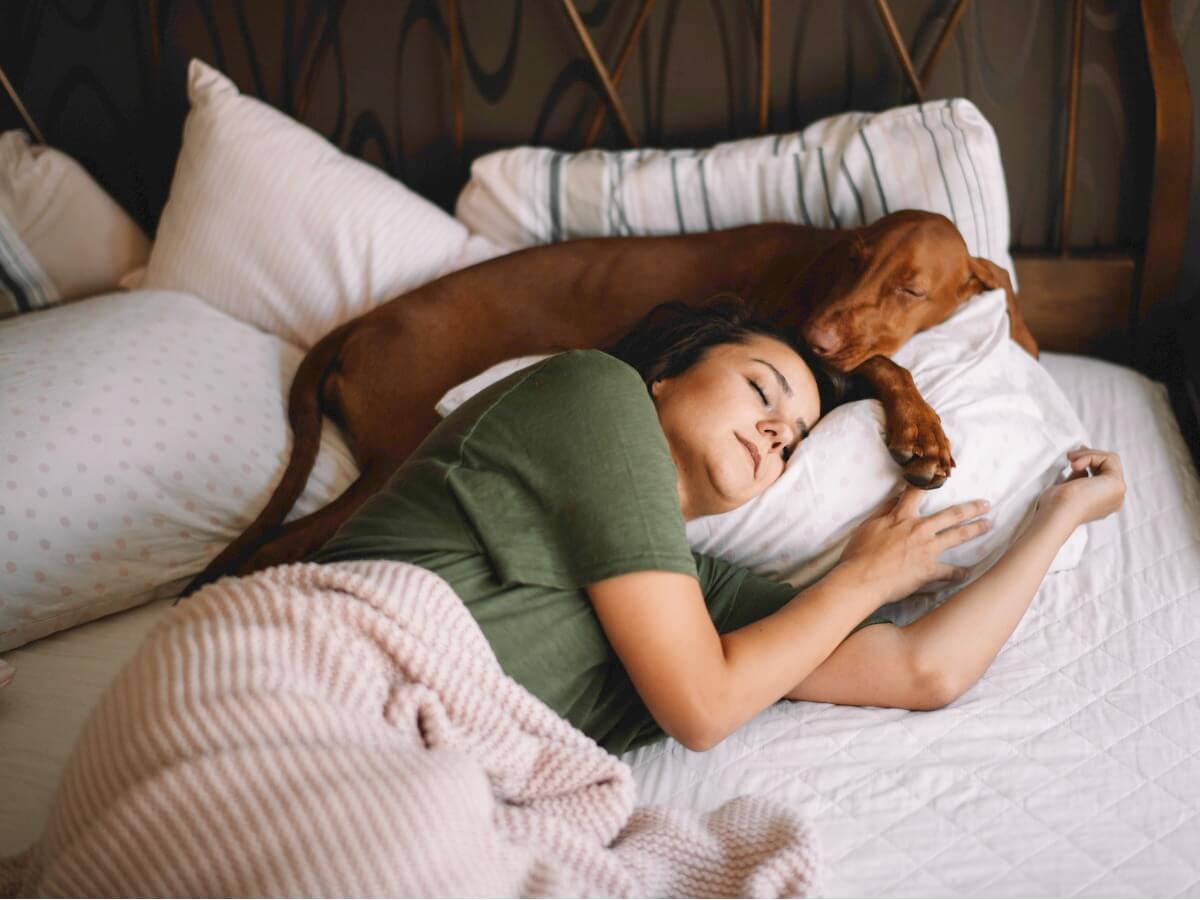 Une fille dort avec son chien.