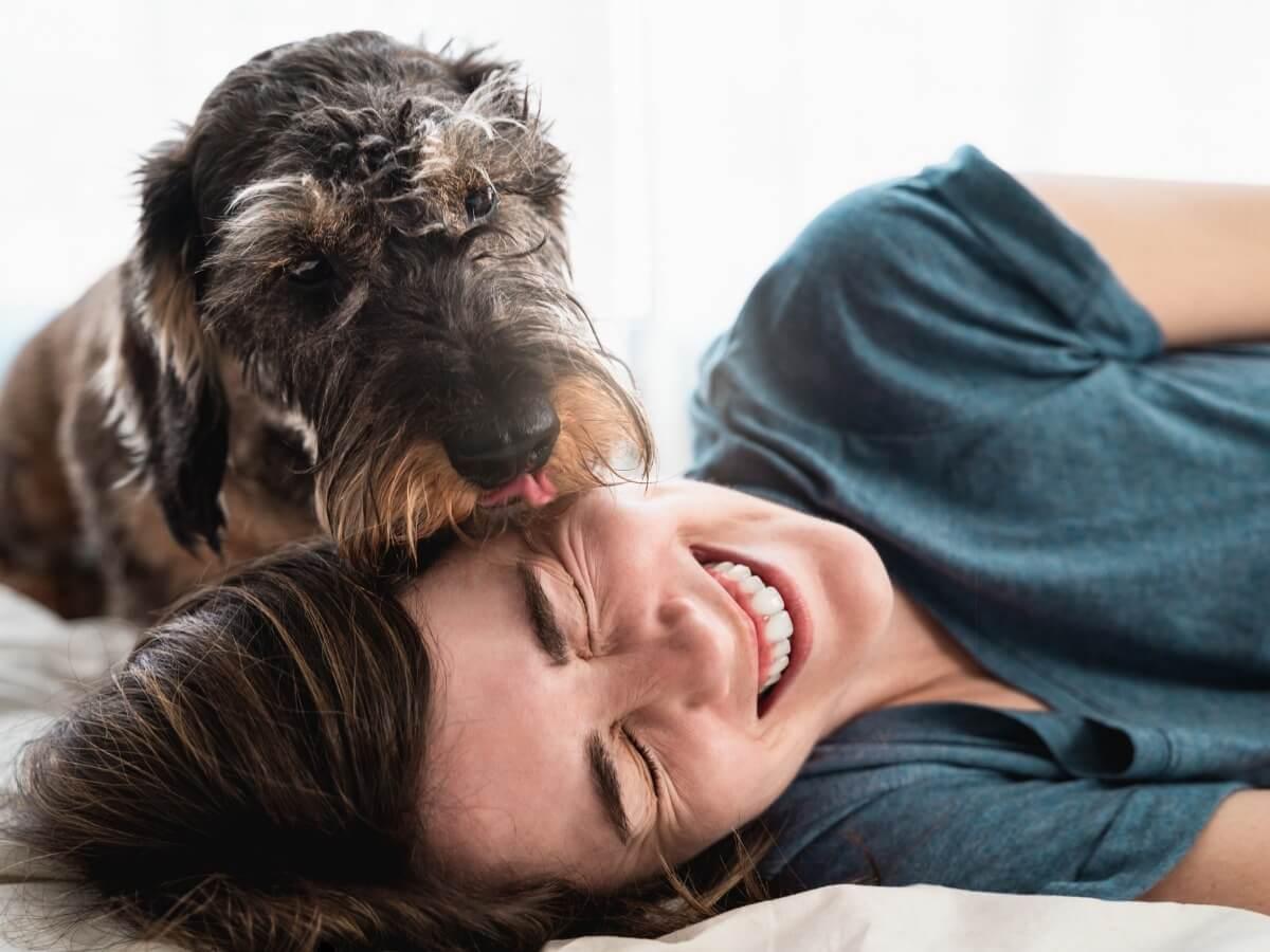 Una mujer juega con su perro.